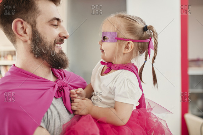 Father and daughter playing super hero and superwoman