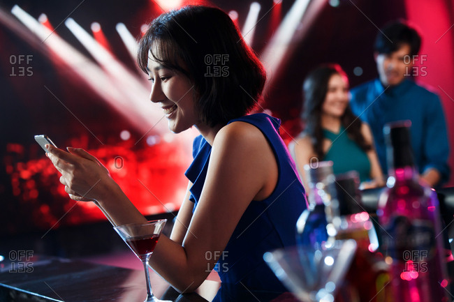 Young women watch phone in the bar