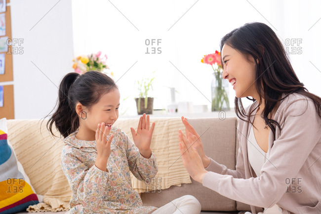 Happy mother and daughter playing at home