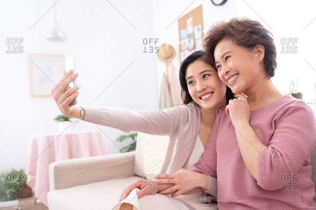 Happy mother and daughter to use mobile phones