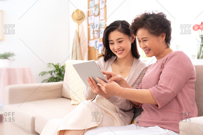Happy mother and daughter see tablets