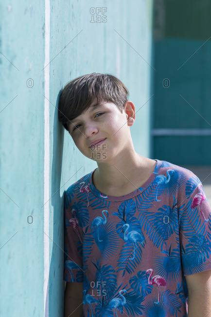 Portrait of cheerful boy leaning on wall while looking camera in a sunny day