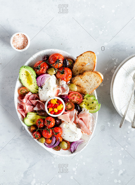 Fresh burrata cheese baked and fresh tomatoes, avocado, pickled peppers and charcuterie meat. Antipasto plate or healthy breakfast, top view