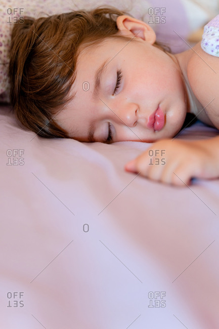Little girl sleeping with sweet face on bed