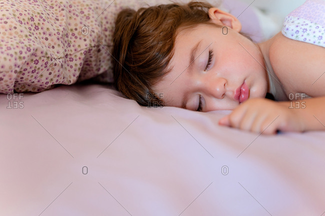 Two years old little girl sleeping with sweet face on bed