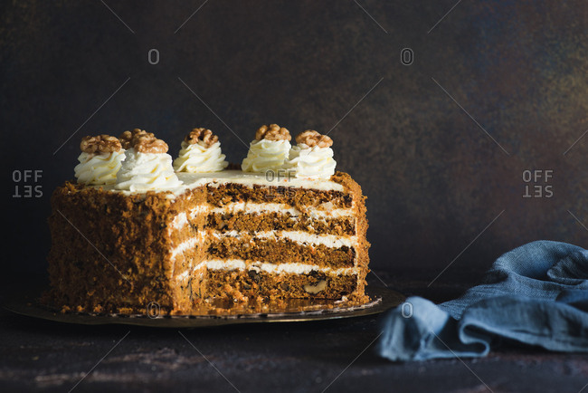Sliced carrot cake with nuts on a plate against a dark background