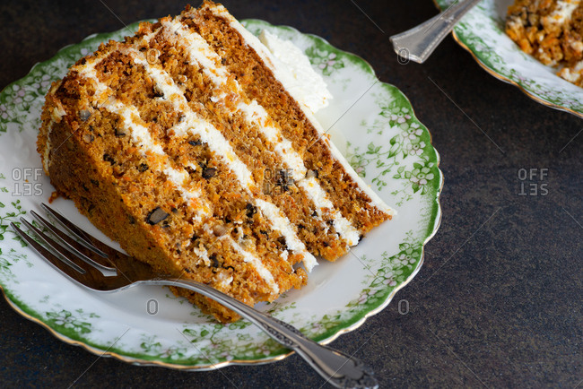 Slice of carrot cake with walnuts on plate