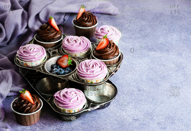 Chocolate and blueberry cupcakes with cream cheese frosting in vintage metal pan