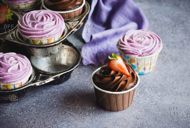 Chocolate and blueberry cupcakes with cream cheese frosting, selective focus