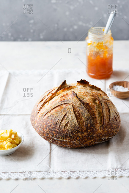Crusty loaf of sourdough bread with jar of orange jam and butter over vintage napkin