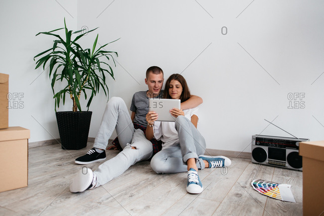 Moving in - couple in love sitting on floor in empty room of their new house. Young man and woman planning design of their new home with digital tablet and color swatches.