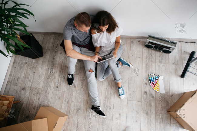 Relocation - couple sitting on floor in empty room of their new house. Top view of young man and woman planning design of their new home with digital tablet and color swatches.