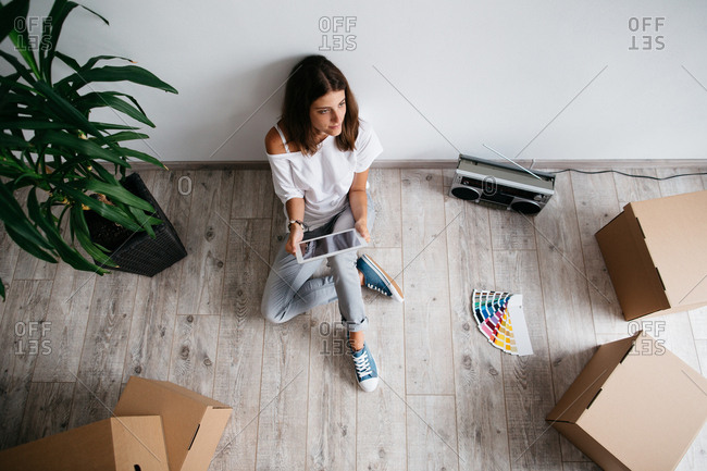 Young woman sitting on floor in empty room of her new house. High angle view of woman planning interior of her new home with digital tablet and color swatches.