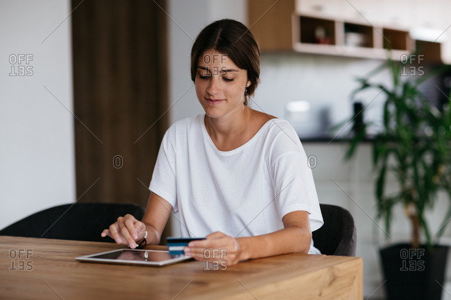 Online payment - young woman paying online with credit card at home. Cheerful woman paying bills online using digital tablet.