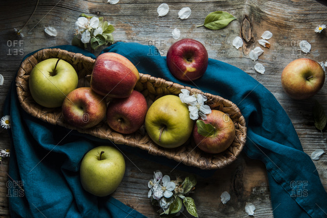 Green and red apples with apple tree flowers on a wooden background