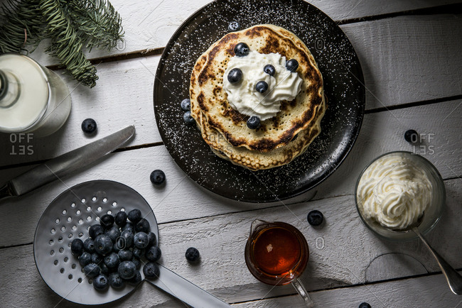 Pancakes topped with cream and blueberries
