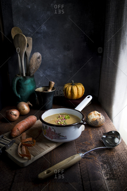 Vegetables soup in a pan on a kitchen wooden worktop in front of a window