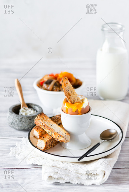Soft-boiled egg for breakfast, salt, toasted bread and roasted vegetables on side