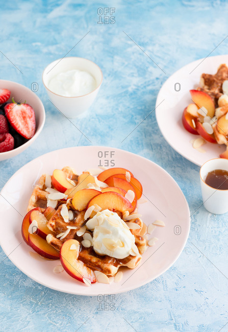 Fresh Belgian Liege waffles served with yellow plums, whipped cream and almonds