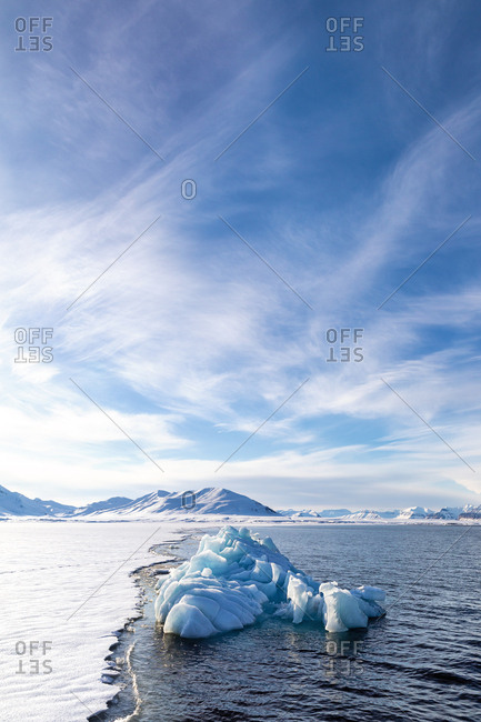 Blue glacial iceberg at the edge of the fast ice, Svalbard.