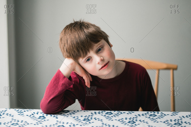 Boy sitting alone at a table laying his head on his hand.