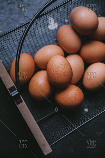 Wire and wooden basket filled with brown eggs.