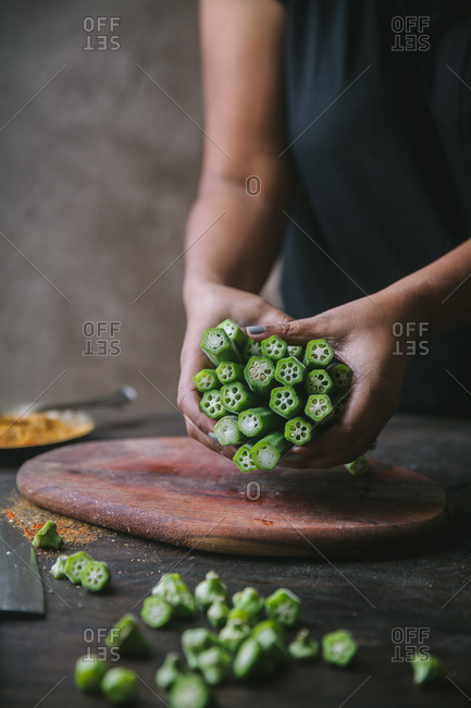 Woman holding chopped okra over wooden cutting board.