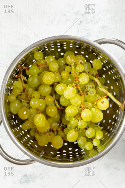 Branch of grapes in colander on white background top view