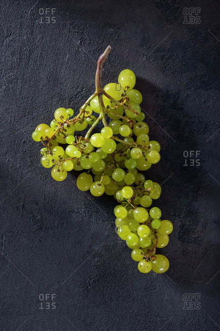 Branch of sultana grapes on dark background top view