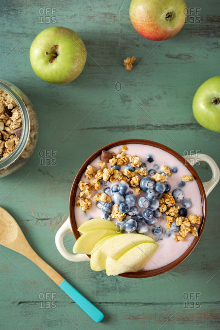 Bowl granola with vegetarian yogurt, apples and blueberries