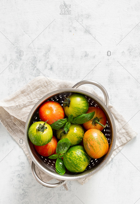 Washed various tomatoes in a colander on a white background