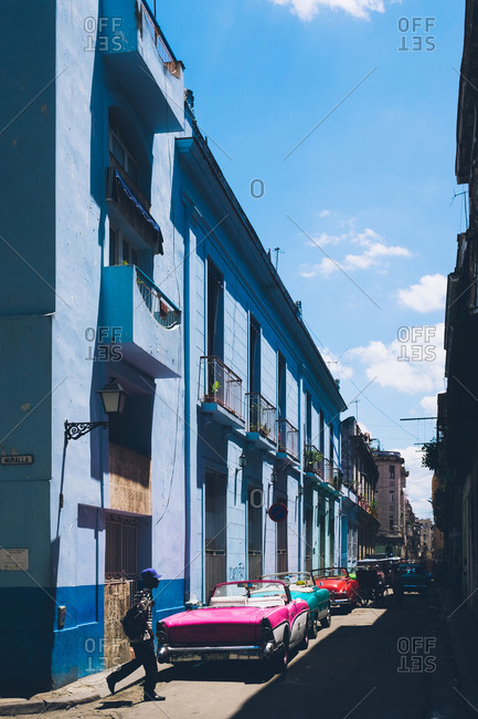 Havana, Cuba - April 17, 2019: Street scene in Havana with blue building and old cars