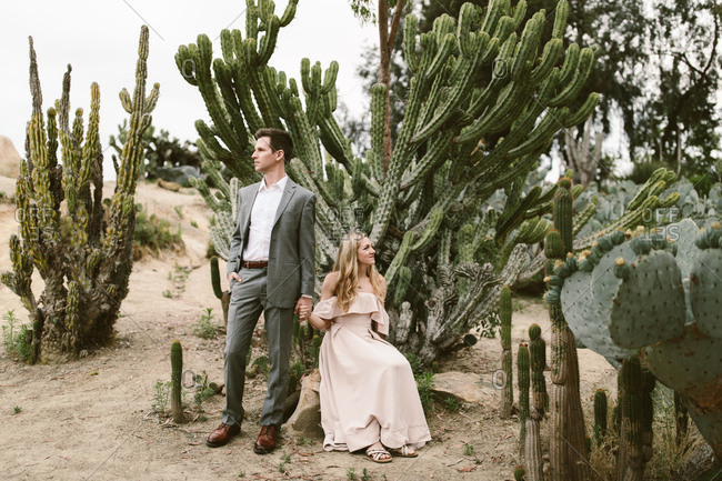Nicely dressed couple holding hands in front of a cactus