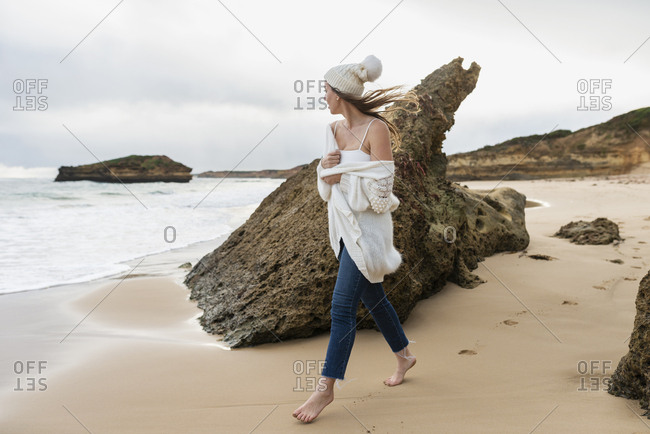Woman looking at the ocean while walking on beach on a windy cold winter day in Australia