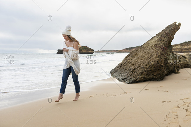 Woman walking on beach on a windy cold winter day in Australia