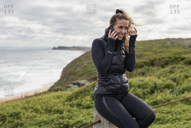 Woman sitting by ocean talking on her phone