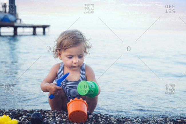 Baby girl playing in the pebbles on a beach