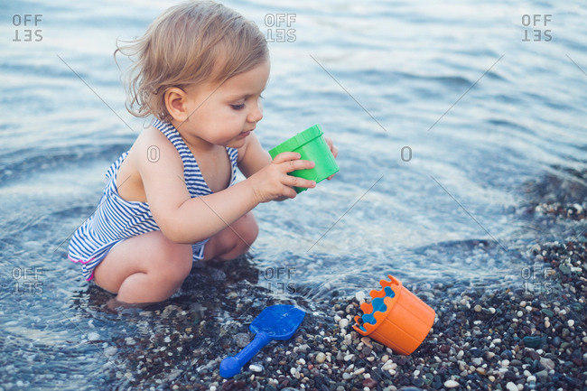Baby playing in the pebbles on a beach
