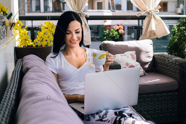 Smiling woman using laptop and drinking coffee on balcony
