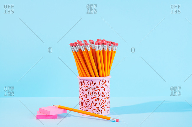 Closeup of the ends of sharpened pencils with sticky note pad on blue background