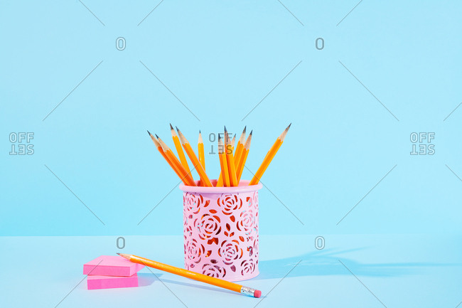 Sharp pencils in pink desk container with sticky notes on blue background