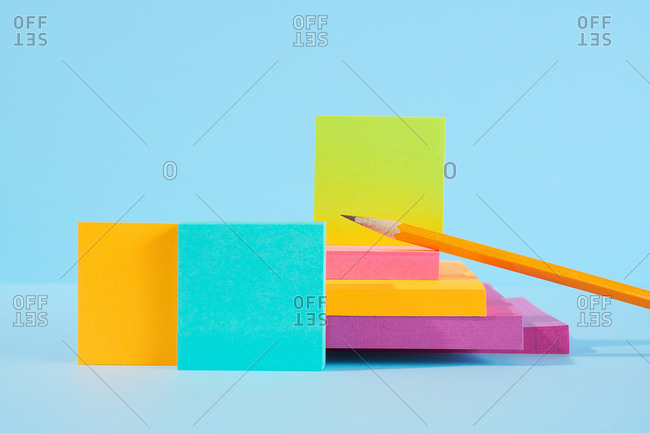 Pencils and various color sticky notes on blue background