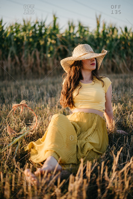 Pretty woman with flaxen hat sitting on a field of hay and relaxing
