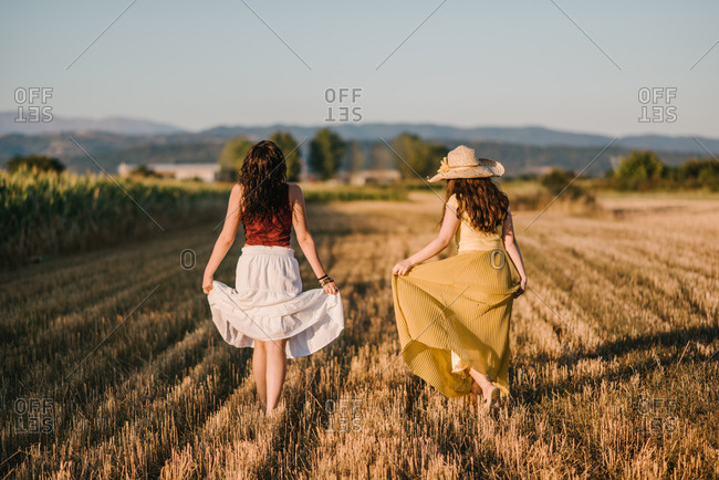 Two pretty countrygirls walking on a field