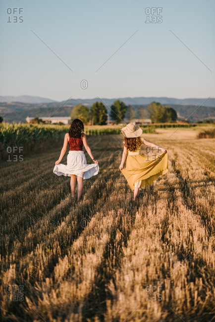 Countrygirls in skirts walking on a yellow field