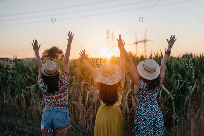 Three young women waving to a sunset in a beautiful scenery