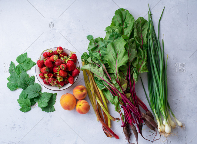 Fresh fruits and vegetables from the farm - beets, rhubarb, onions, peaches and strawberry with blackcurrant leaves. Harvest season