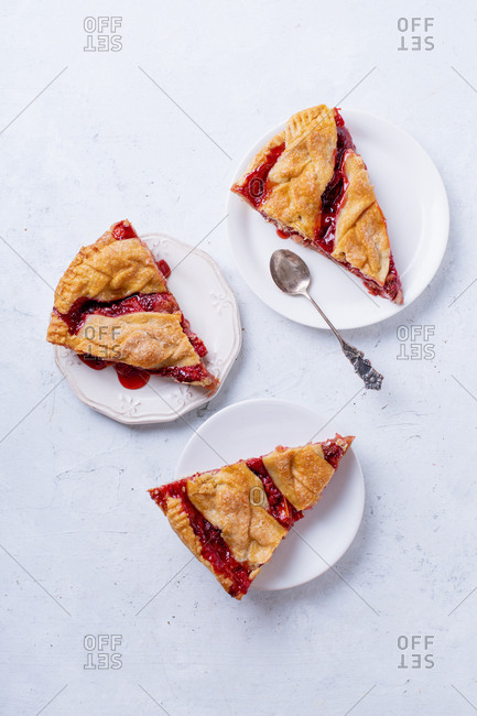 Slices of rhubarb strawberry pie decorated with braided lattice