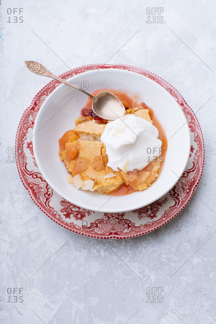Peach cobbler with hot sugar crust and whipped cream