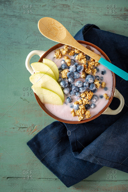 Bowl granola with vegetarian yogurt apples and blueberries